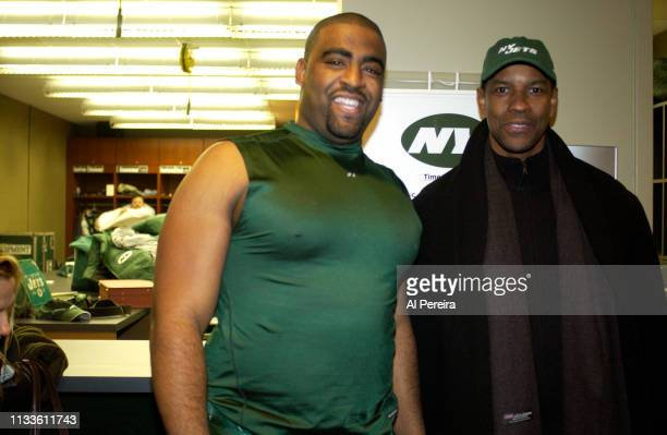 Actor Denzel Washington meets with New York Jets player Alan Harper in the locker room when he attends the New York Jets v Seattle Seahawks game at...