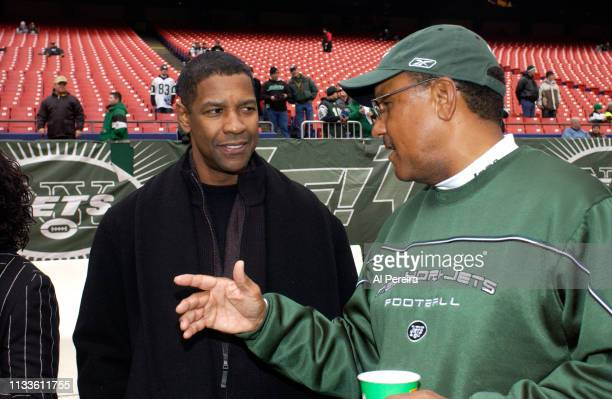 Actor Denzel Washington meets with New York Jets Running Backs Coach Bishop Harris on the New York Jets sideline when he attends the New York Jets v...