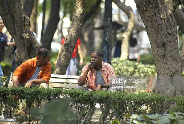 Actor Denzel Washington smokes a cigar while waiting to film a scene from the film Man On Fire as a stuntman sits nearby at Condesa Park April 29...