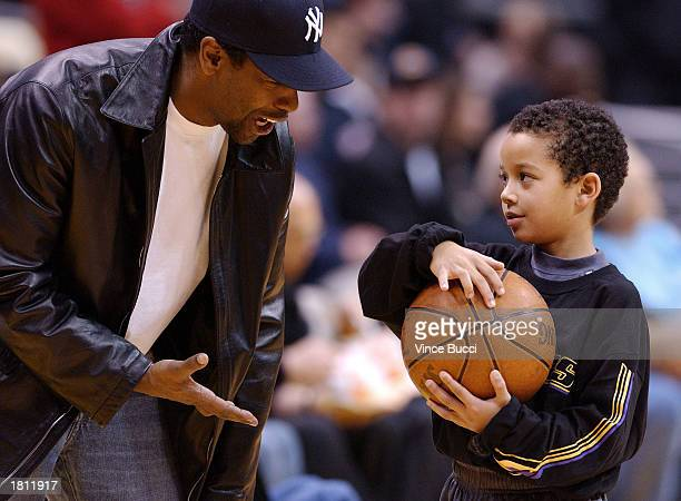 Actor Denzel Washington talks with Devin Fox son of Rick Fox of the Los Angeles Lakers as the Los Angeles Lakers host the Seattle SuperSonics on...