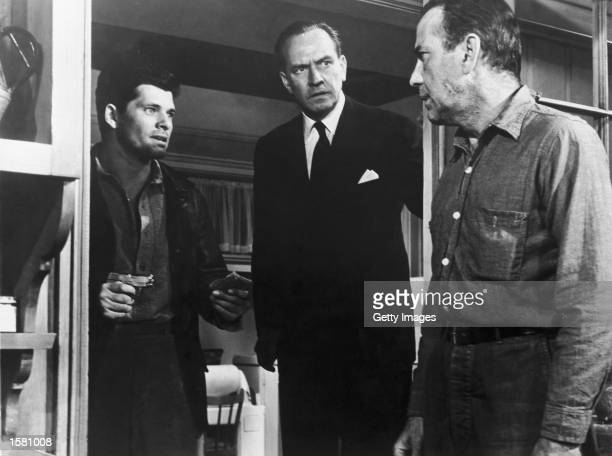 Actor Dewey Martin points a gun and holds a handful of cash as Frederic March and Humphrey Bogart look on in a still from the film 'The Desperate...