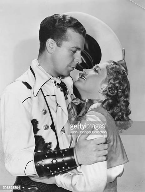 Actor Dick Powell embracing Priscilla Lane in costumes from the 1938 film Cowboy from Brooklyn
