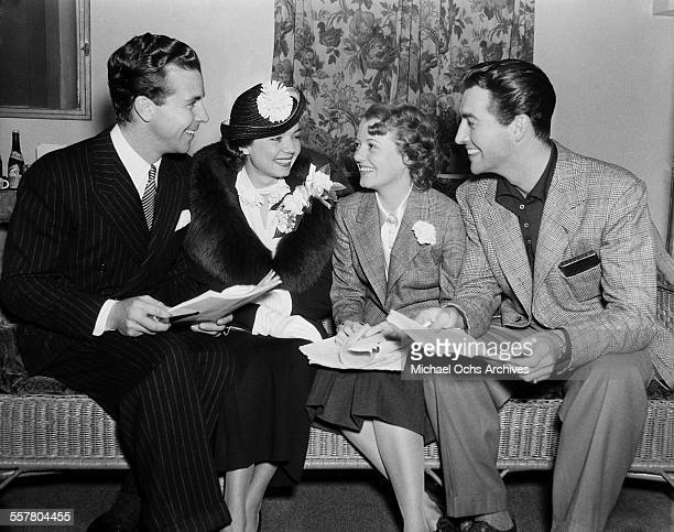 Actor Dick Powell talks with actress Frances Langford actress Janet Gaynor and actor Robert Taylor in Los Angeles California