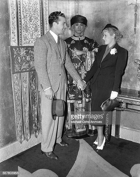 Actor Dick Powell with his wife actress Joan Blondell attend an event at Grauman's Chinese Theatre in Los Angeles, California.