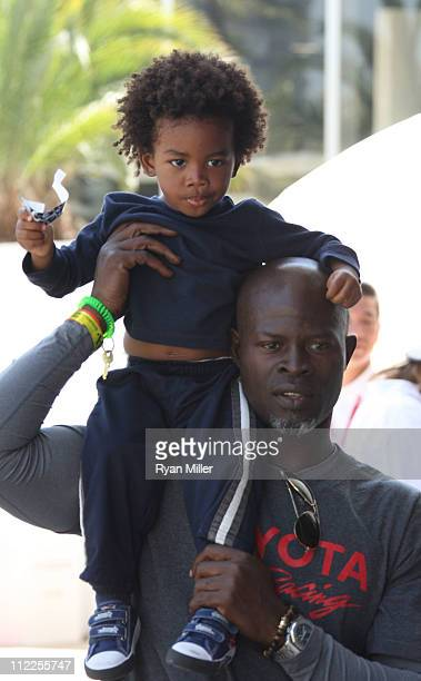 Actor Djimon Hounsou holds son Kenzo Lee Hounsou on his shoulders during the 35th Annual Toyota Pro/Celebrity Race at the Long Beach Grand Prix on...