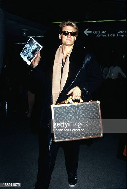 Actor Dolph Lundgren holds an autographed photo of himself and a Louis Vitton suitcase at LAX airport in 1986 in Los Angeles California