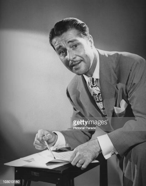 Actor Don Ameche cohost of 'The Frances LangfordDon Ameche Show' examining a script for the show USA circa 1951