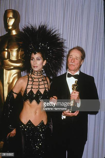 Actor Don Ameche holds his Best Supporting Actor Oscar while posing with Cher at the Academy Awards Los Angeles California March 24 1986 Ameche won...