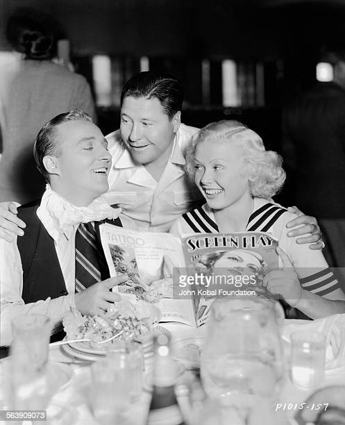 Actor Don Ameche leaning over actor Bing Crosby and an actress who are sitting at a table together for Paramount Pictures 1942