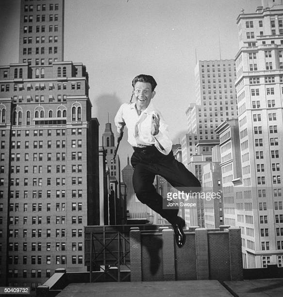 Actor Donald O'Connor holding walking stick and energetically leaping into the air as he dances in front of painted city backdrop probably part of...