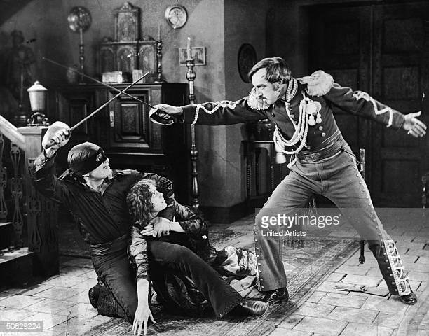 Actor Douglas Fairbanks crouches with his arm around Marguerite De La Motte while dueling villain Robert McKim in a still from the film 'The Mark of...