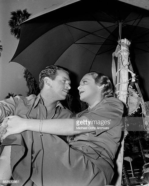 Actor Douglas Fairbanks Jr poses with Mary Lee Eppling under an umbrella in Los Angeles California