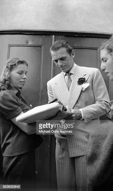 Actor Douglas Fairbanks Jr signs papers in Los Angeles California
