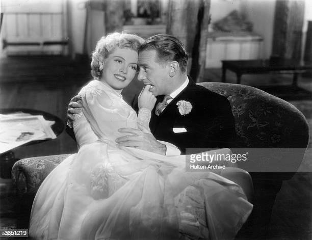 Actor Douglas Fairbanks Junior nibbles seductively on Yolande Donlan's finger in a love scene from the United Artists film 'Mr Drake's Duck'.