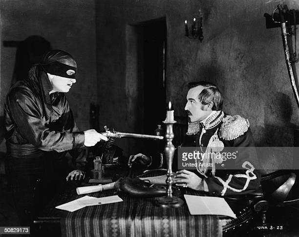 Actor Douglas Fairbanks points a rifle at actor Robert McKim in a still from the film 'The Mark of Zorro' directed by Fred Niblo 1920