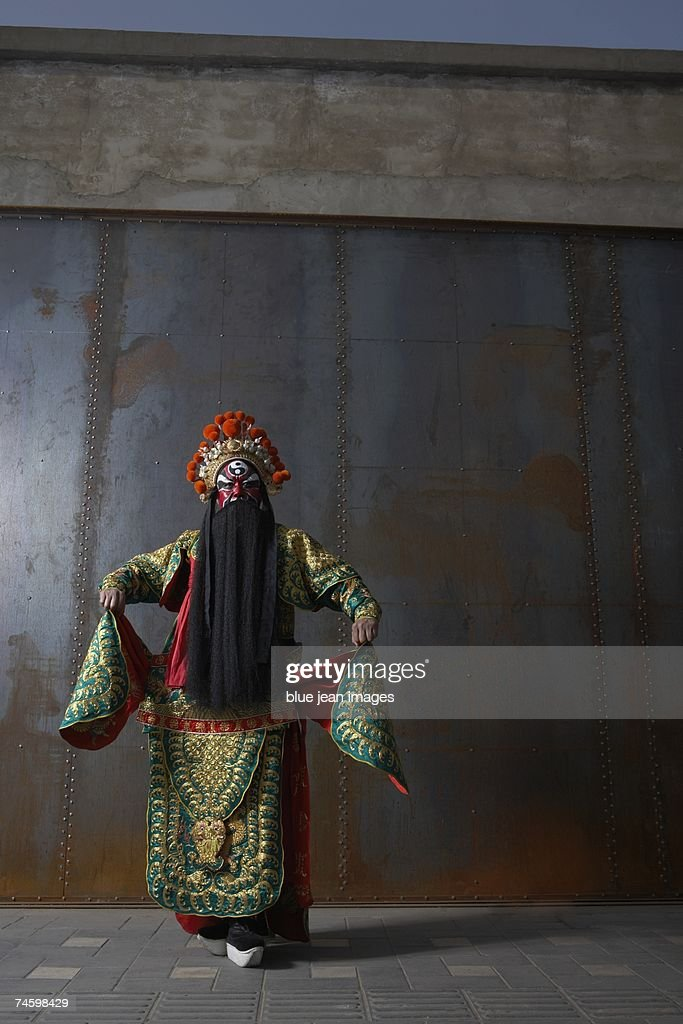 Actor dressed as a traditional Beijing Opera Army General dances in front of an industrial rusting steel wall. : Stock Photo