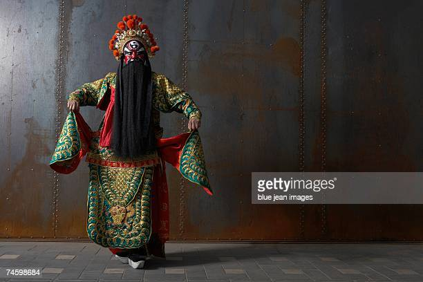 actor dressed as a traditional beijing opera army general dances in front of an industrial rusting steel wall. - beijing opera stock photos and pictures