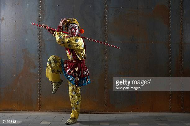 Actor dressed as traditional Beijing Opera comedian poses on one leg with a staff in front of an industrial rusting steel wall.
