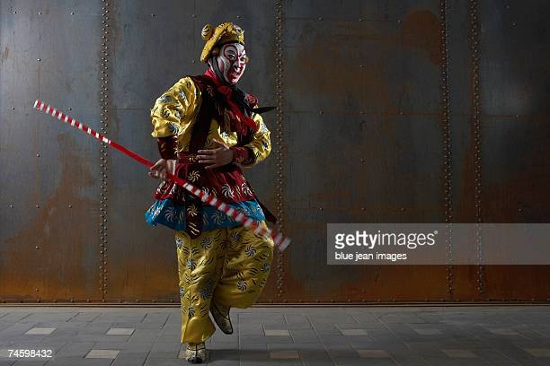 actor dressed as traditional beijing opera comedian spins a staff in front of an industrial rusting steel wall. - beijing opera stock photos and pictures