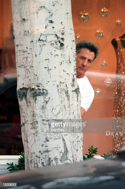 Actor Dustin Hoffman plays peek-a-boo with the paparazzi while shopping with his daughter December 19, 2000 in Beverly Hills, CA