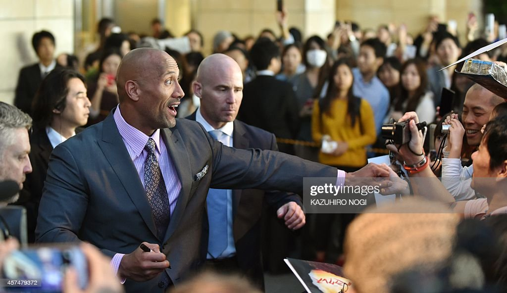 US actor Dwayne Johnson (L) is greeted by Japanese fans upon his arrivalat the red carpet ceremony for the Japan premiere of 'Hercules' in Tokyo on October 19, 2014. The film will open across Japan on October 24.