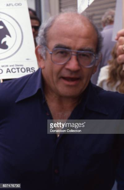 Actor Ed Asner smokes a cigarette as he holds a SAG and AFTRA Actors On Strike picket sign in circa 1980 in Los Angeles California