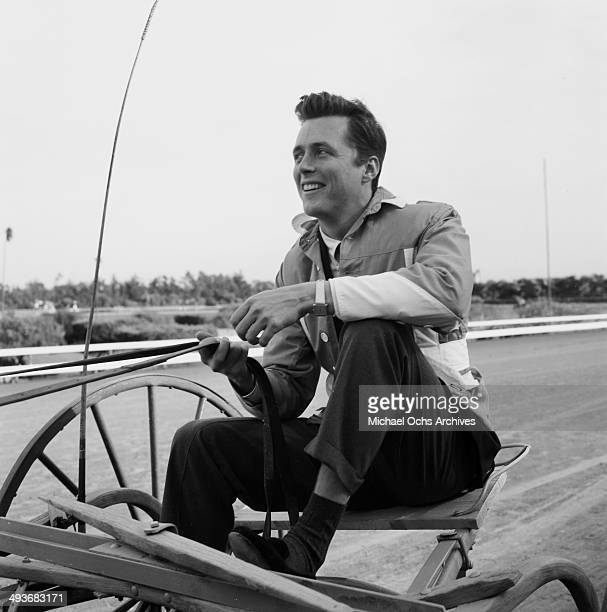 Actor Edd Byrnes rides on a racing horse buggy in Los Angeles, California.