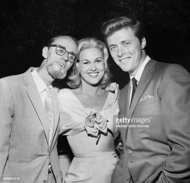 Actor Edd Byrnes with his wife actress Asa Maynor pose with photographer Earl Leaf at a party in Los Angeles, California.