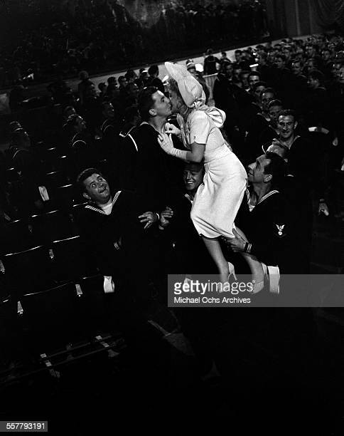 Actor Eddie Bracken kisses Betty Hutton during filming of Star Spangled Rhythm in Los Angeles California