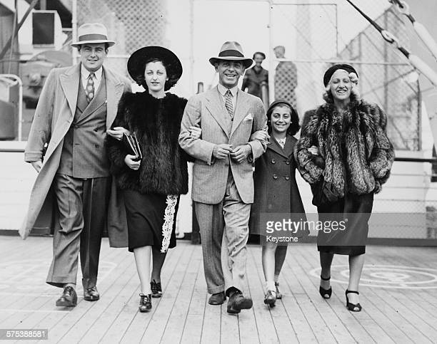 Actor Eddie Cantor arm in arm with his wife daughters and soninlaw on the deck of their ship as it arrives in Southampton July 11th 1938