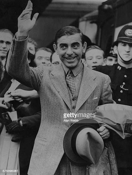 Actor Eddie Cantor waves to the crowd that have come to greet him as he arrives at Waterloo Station London July 11th 1938