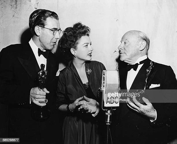 Actor Edmund Gwenn and writer George Seaton holding their Oscars for the film 'Miracle on 34th Street' with presenter Anne Baxter at the 20th Academy...
