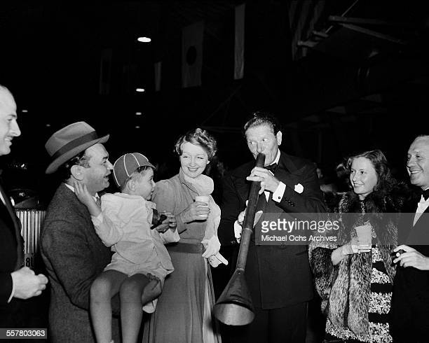 Actor Edward G Robinson holds a little boy gossip columnist Hedda Hopper Danny Kaye plays a horn and Jack Benny smiles during an event in Los Angeles...