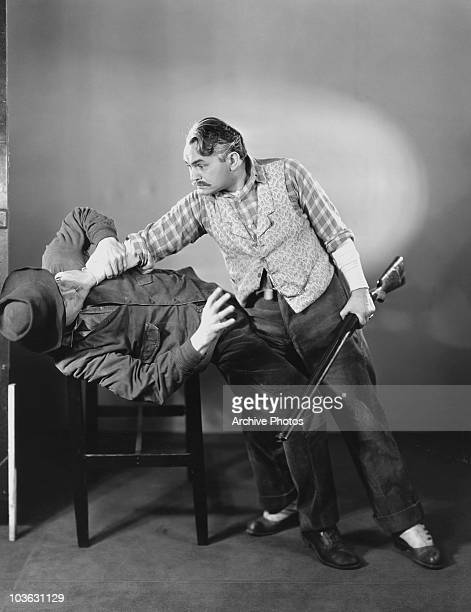 Actor Edward G Robinson pictured holding a rifle in his left hand while holding a man around the neck with his right hand in a scene from the film 'A...