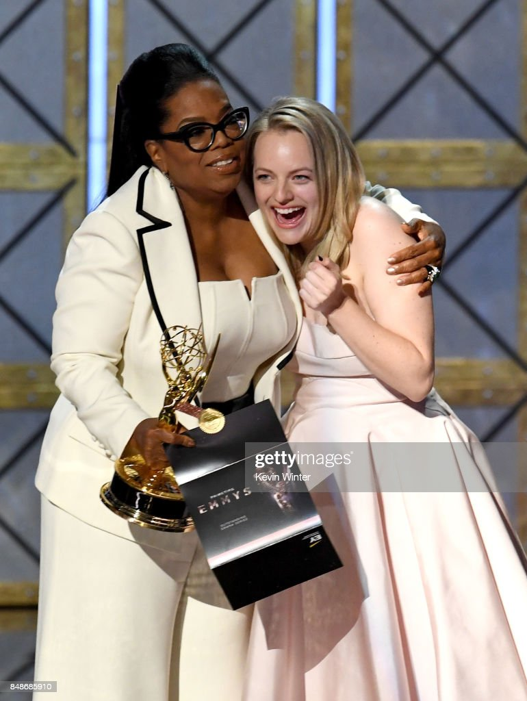 Actor Elisabeth Moss (R) accepts Outstanding Drama Series for 'The Handmaid's Tale' from Oprah Winfrey onstage during the 69th Annual Primetime Emmy Awards at Microsoft Theater on September 17, 2017 in Los Angeles, California.