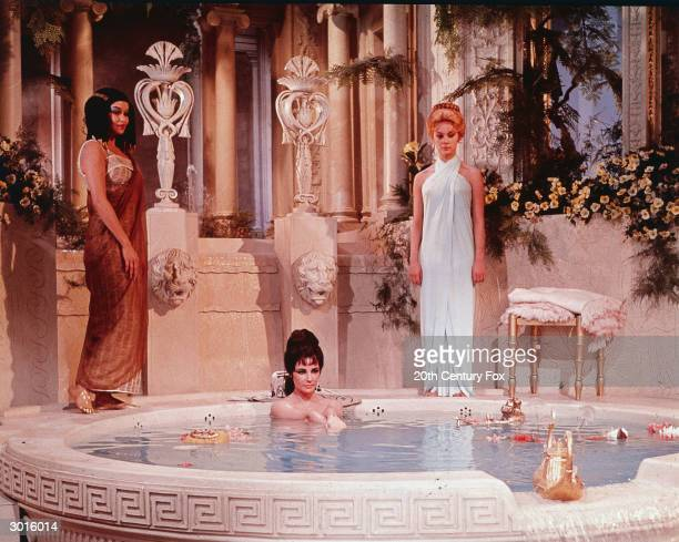 Actor Elizabeth Taylor takes a bath in a tub with two unidentified women behind her in a still from the film, 'Cleopatra,' directed by Joseph...