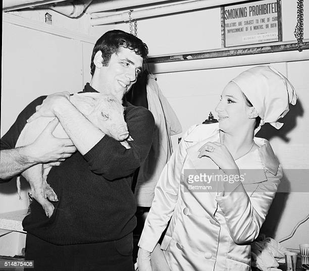 Actor Elliott Gould gives wife Barbra Streisand a piglet on her birthday as an opening night good luck charm. New York, 1966.
