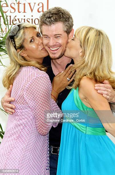 Actor Eric Dane shares a kiss with TV presenter Rachel Bourlier and actress Nathalie Vincent during a photo call promoting the television series...