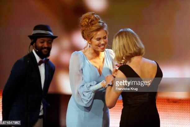 Actor Eric Kabongo and actress Palina Rojinski award editor Heike Parplies for Best Editor at the Lola German Film Award show at Messe Berlin on...