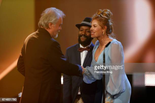 Actor Eric Kabongo and actress Palina Rojinski congratulate Reinhold Vorschneider on stage at the Lola German Film Award show at Messe Berlin on...
