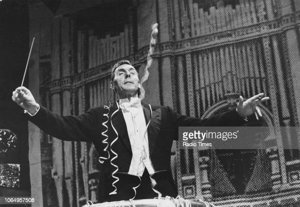 Actor Eric Sykes conducting an orchestra in front of a 'Royal Albert Hall' backdrop in a scene from the television sitcom 'Sykes' circa 1975