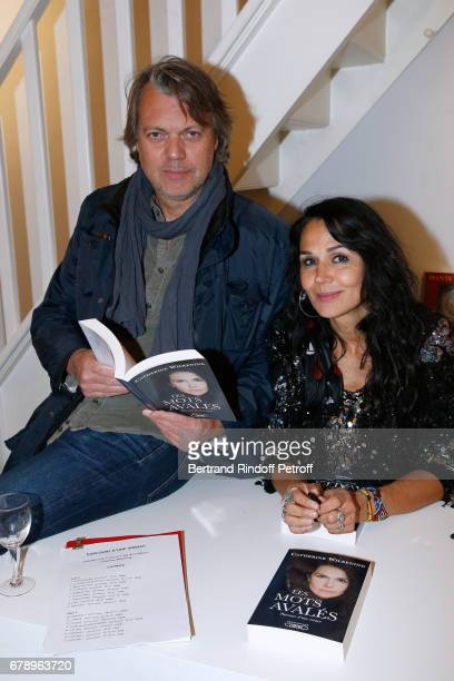 Actor Eric Viellard and actress Catherine Wilkening attend Catherine Wilkening signs her book Les mots avales and exhibits her works at Galerie...