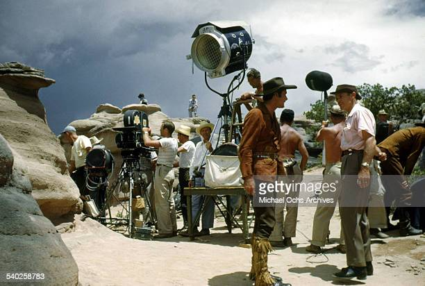 Actor Errol Flynn gets ready on set as a film crew films the movie 'Rocky Mountain' on location in Gallop New Mexico Starring Errol Flynn and Patrice...