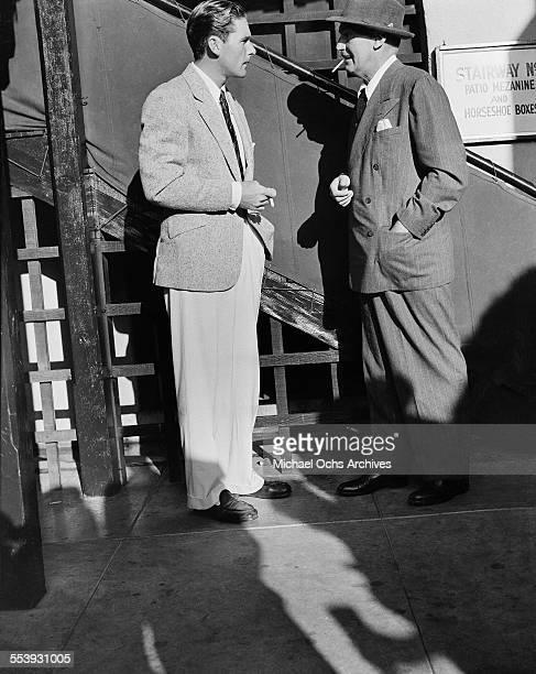 Actor Errol Flynn seen talking on a studio back lot in Los Angeles California