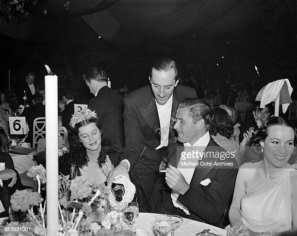 Actor Errol Flynn sits at a table as actor Basil Rathbone pours champagne for him with Veronica Cooper and actress Dolores Del Rio during an event in...