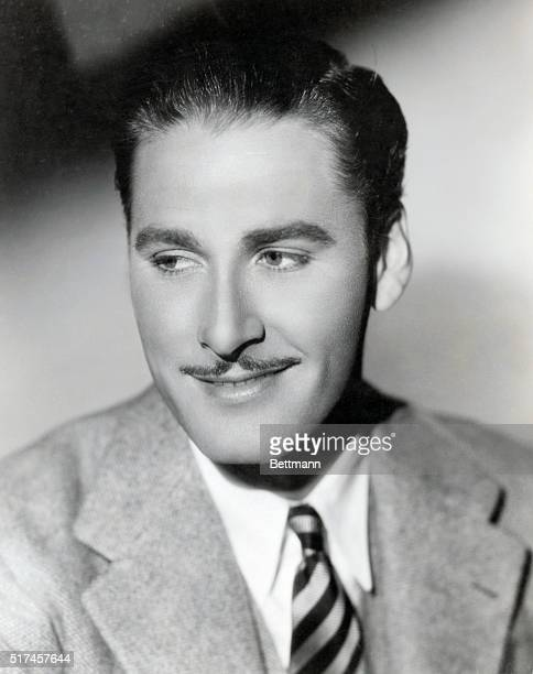 Actor Errol Flynn wearing suit and tie and sporting his famous mustache