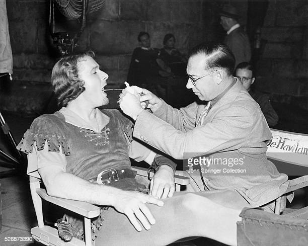 Actor Errol Flynn who plays the title role in Warner Brothers The Adventures of Robin Hood has his throat sprayed by Dr McWilliams between scenes of...