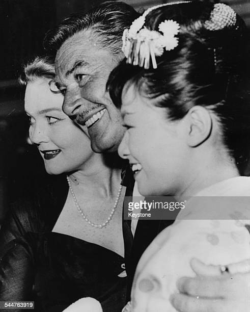 Actor Errol Flynn with his arms around his wife Patrice Wymore and actress Izumi Yukimura at the Berlin Film Festival June 24th 1957