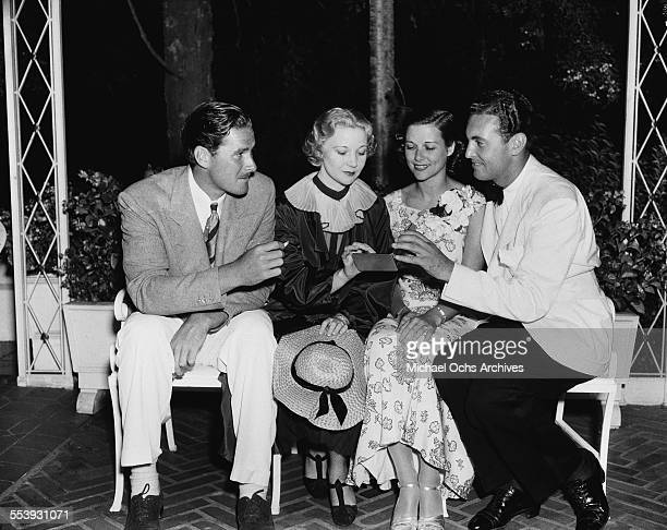 Actor Errol Flynn with wife Lili Damita sit on a bench with another couple in Los Angeles California