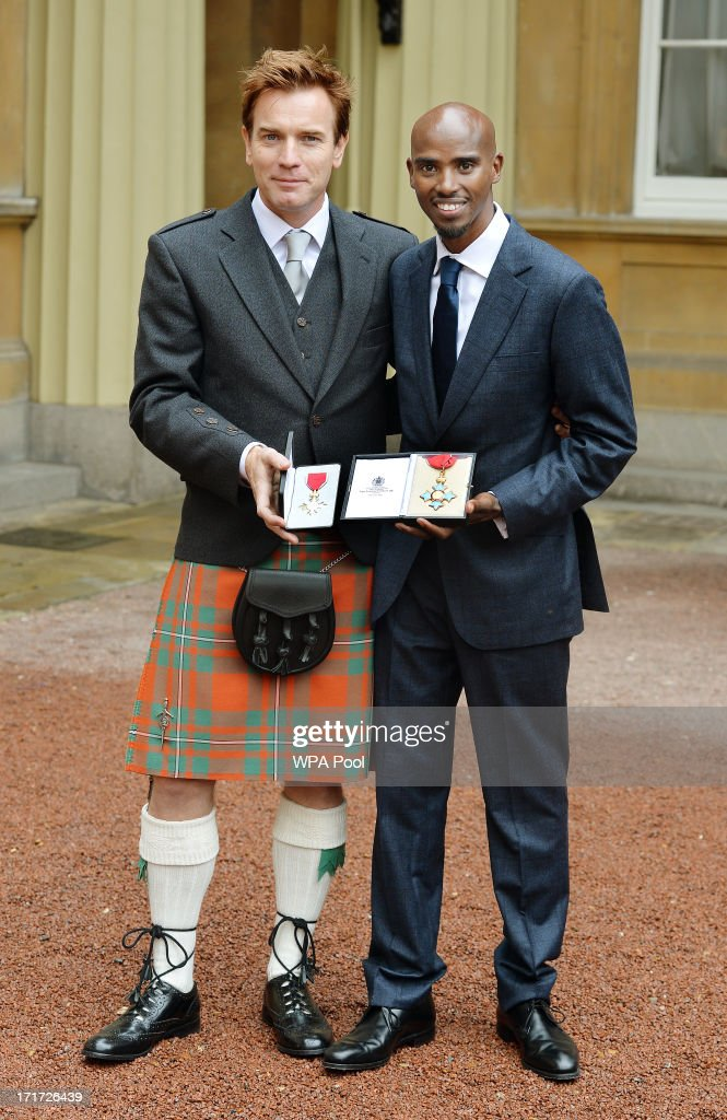 Actor Ewan McGregor holds his OBE with Double Olympic Gold Medal winning athlete Mo Farrah as he holds his CBE after they received the awards from Prince Charles, Prince of Wales during an Investiture ceremony at Buckingham Palace on June 28, 2013 in London, England. Mo Farah will receive an CBE for services to Athletics.